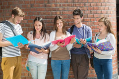 Happy students standing and reading Stock Image