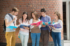 Happy students standing and reading Stock Images