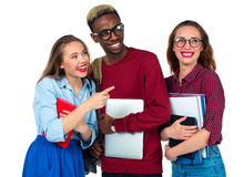 Happy students standing and smiling with books, laptop and bags Royalty Free Stock Images
