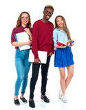 Happy students standing and smiling with books, laptop and bags Stock Photo