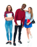 Happy students standing and smiling with books, laptop and bags Royalty Free Stock Photo