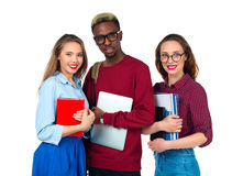 Happy students standing and smiling with books, laptop and bags Royalty Free Stock Photography