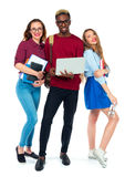Happy students standing and smiling with books, laptop and bags Stock Photos