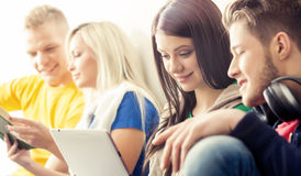 Happy students with a tablet computer. Social network and internet concept Stock Photography