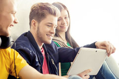 Happy students with a tablet computer. Social network and internet concept Royalty Free Stock Images