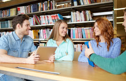Happy students with tablet pc in library Stock Image