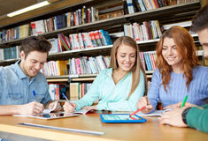 Happy students with tablet pc in library Stock Images