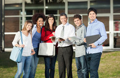 Happy Students With Teacher Standing On College. Portrait of happy multiethnic students with teacher standing on college campus Stock Photos