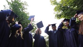 Happy students throwing mortar boards up stock video