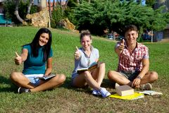 Happy students thumb up in college Royalty Free Stock Photography