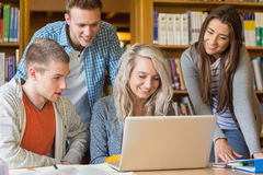 Happy students using laptop at desk in library Stock Images