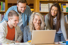 Happy students using laptop at desk in library Royalty Free Stock Photo