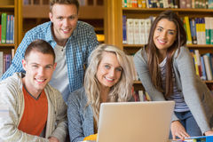 Happy students using laptop at desk in library Royalty Free Stock Photography