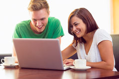 Happy students using laptop while having coffee at  coffee shop Royalty Free Stock Photography