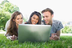 Happy students using laptop outside Stock Image