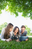 Happy students using tablet pc outside Stock Images