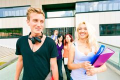 Happy Students Walking Out Of College. Group of happy students walking out of college Stock Photography