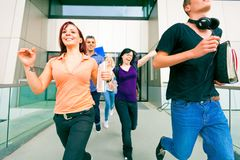 Happy Students Walking Out Of College. Group of happy students walking out of college Stock Image