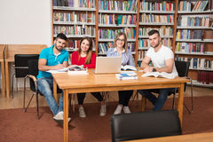 Happy Students Working With Laptop In Library. In The Library - Handsome Group Of Students With Laptop And Books Working In A High School - University Library Royalty Free Stock Images