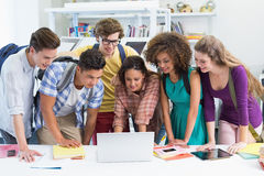 Happy students working together on laptop Royalty Free Stock Images