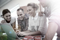 Happy students working together on a laptop Royalty Free Stock Photo