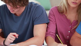 Happy students writing on notebooks Royalty Free Stock Photos
