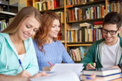 Happy students writing to notebooks in library Royalty Free Stock Image