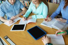 Happy students writing to notebooks in library Royalty Free Stock Photo