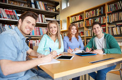 Happy students writing to notebooks in library Stock Image