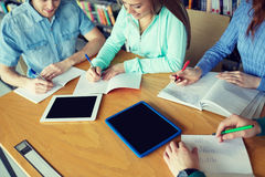 Happy students writing to notebooks in library Royalty Free Stock Photography