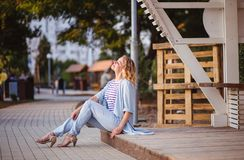 Happy stunning curly blonde girl with beautiful smile sitting in the city street. stock image