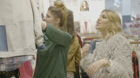Happy styled female friends checking a designer bag an looking at clothing items to shop in a brand store at the mall -. Happy styled female friends checking a stock footage