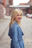 Happy Stylish Adult Blond Woman at the Street. Stylish Adult Blond Woman in Blue Dress Standing at the Street and Looking at the Camera with a Smile Royalty Free Stock Photography