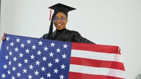 Happy stylish afro american female student in graduate uniform holding US flag in front of her. The average plan