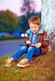 Happy stylish boy playing on media tablet in city park Stock Photo