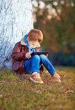 Happy stylish boy playing on media tablet in city park Royalty Free Stock Image