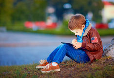Happy stylish boy playing on media tablet in city park Royalty Free Stock Photos