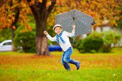 Happy stylish boy with umbrella running in park Royalty Free Stock Images