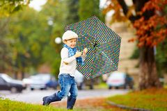 Happy stylish boy with umbrella running in park Royalty Free Stock Image