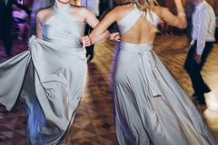 Happy stylish bride and bridesmaids dancing and having fun at we. Dding reception in restaurant. guests dancing in light, people in motion at party in club. fun stock photos