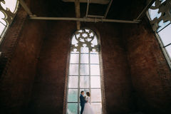 Happy stylish bride and groom holding each other in the belltower of old gothic cathedral Stock Photos
