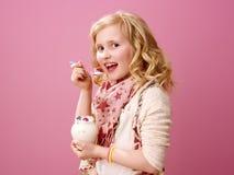 Happy stylish child isolated on pink eating farm organic yogurt. Pink mood. happy stylish child with wavy blonde hair isolated on pink eating farm organic yogurt Royalty Free Stock Photography