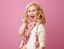 Happy stylish child isolated on pink eating farm organic yogurt. Pink mood. happy stylish child with wavy blonde hair isolated on pink eating farm organic yogurt Stock Photo