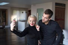 Happy stylish couple in black outfit taking selfie indoor. Happy young stylish couple in black outfit taking selfie indoor stock photo