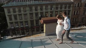 Happy stylish couple bride and groom walking on the roof. stock footage