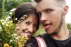 Happy stylish couple taking selfie and having fun in meadow with royalty free stock image