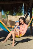 Happy stylish family with cute daughter relaxing in hammock on summer vacation in evening sun light on the beach. hipster couple w. Ith child resting and having royalty free stock photo