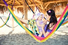 Happy stylish family with cute daughter relaxing in hammock on summer vacation in evening sun light on the beach. Hipster couple with child resting and having stock image