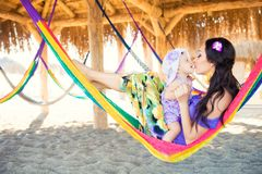 Happy stylish family with cute daughter relaxing in hammock on summer vacation in evening sun light on the beach. Hipster couple with child resting and having stock photo