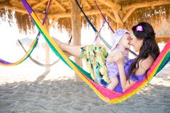 Happy stylish family with cute daughter relaxing in hammock on summer vacation in evening sun light on the beach. hipster couple w. Ith child resting and having royalty free stock images